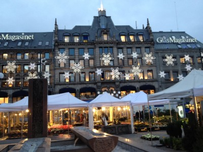 """Retailers have suddenly seen a rise in Christmas shopping. Shown here, the venerable """"GlasMagasinet"""" department store in downtown Oslo, now part of a shopping center inside the historic building, with the city's open-air flower market in the foreground. PHOTO: John Smith, for Views and News"""