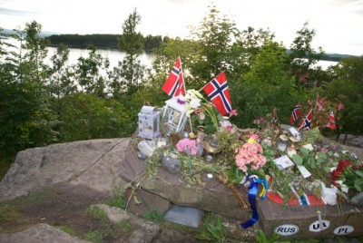 Fresh flowers, new flags and mementos are still being left at this site across from Utøya, where 69 persons were killed and hundreds more injured and traumatized last summer. PHOTO: Views and News