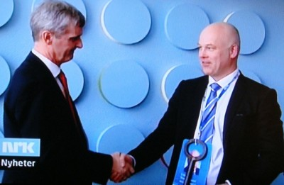 """Thor Gjermund Eriksen, with the symbolic key to his new office around his neck, was wished well by his predecessor Hans-Tore Bjerkaas on NRK's own nightly national news program """"Dagsrevyen"""" Monday evening. PHOTO: NRK screen grab/newsinenglish.no"""