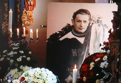 """A large photo of Hjalmar """"Hjallis"""" Andersen wearing one of his many victory wreaths was on display along with a bounty of flower wreaths, many shaped like hearts. PHOTO: NRK screen grab/newsinenglish.no"""
