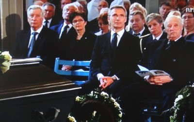 """King Harald and Prime Minister Jens Stoltenberg were among many paying their respects to Hjalmar """"Hjallis"""" Andersen at his state funeral on Thursday. At far left, Finance Minister Sigbjørn Johnsen. Behind Stoltenberg were local mayors and the heads of several Norwegian athletics associations. Norwegian Broadcasting (NRK) carried the entire funeral live nationwide. PHOTO: NRK screen grab/newsinenglish.no"""