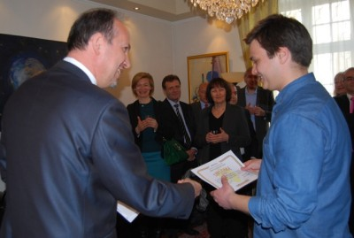 "Romanian Ambassador Daniel Ionita delivering one of five diplomas to Horia Cernusca at the embassy on Monday, part of an effort to showcase ""Young and Successful Romanians in Norway."" PHOTO: newsinenglish.no"