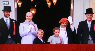 "The Norwegian royal family was once again in place on the palace balcony to wave to the masses on the 17th of May. They've played a major role in encouraging integration and acceptance of Norway's new multi-cultural society, with the late King Olav V among the first to call immigrants ""our new countrymen."" From left: Crown Prince Haakon, Crown Princess Mette-Marit, Prince Sverre Magnus, Princess Ingrid Alexandra, Queen Sonja and King Harald. PHOTO: NRK screen grab/newsinenglish.no"