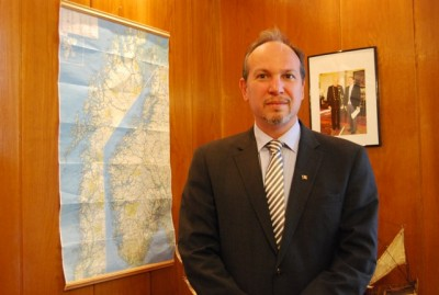 Daniel Ionita, posing with a map of Norway and the king in his office at the Romanian Embassy in Oslo. PHOTO: newsinenglish.no