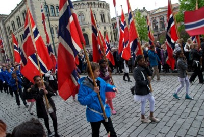 There may not be as many children marching in this year's 17th of May parade in Oslo, but who do are usually enthusiastic. In the background, the Norwegian Parliament downtown. PHOTO: newsinenglish.no