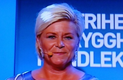 """Siv Jensen, head of the conservative Progress Party, was energetic and on the offense in her own victory speech but also promised to """"give and take"""" during negotiations to form a new government. It will be the first time the Progress Party is part of a government in Norway, and Jensen is widely tipped to be finance minister. PHOTO: NRK screen grab/newsinenglish.no"""