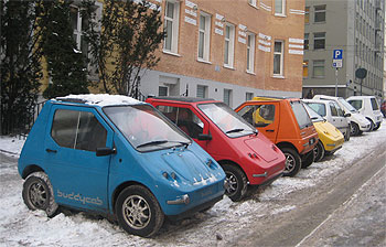 "The compact three-seater ""Buddy"" electric car can fit into motorbike parking spaces, and even park sideways. It's 3 to 5 times more energy efficient than bensin/diesel cars, and has zero emissions of greenhouse gasses.  It has a driving range of 40 to 80 km, depending on the season, terrain and driving style, and its top speed is around 80 km per hour. Developed by developed by Elbil Norge AS, it's still mostly sold in Norway, but international demand is increasing. PHOTO: buddyelectric.no"