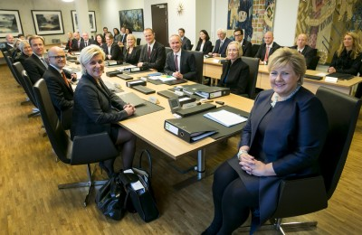 The new government headed by Prime Minister Erna Solberg (at right) posed for one its first official portraits, with fewer ministers around Solberg's table. State secretaries are sitting in the background. PHOTO: Statsministerens kontor
