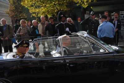 Who rides there? Must be a king! Royal guards, police and military lined up along the parade route were a good indication that King Harald and Queen Sonja would be driving by, in an open car after leaving the opening of parliament. PHOTO: newsinenglish.no
