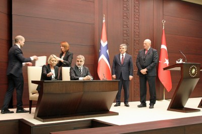 Norway's new minister for business and trade, Monica Mæland, signing an agreement on energy cooperation with her Turkey's energy minister, Taner Yildiz. At far right, King Harald and Turkish President Gül. PHOTO: Nærings- og Handelsdepartementet/Trond Viken