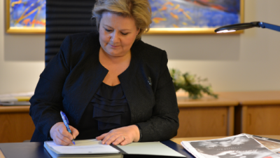 Erna Solberg, shown here signing letters of condolence following Nelson Mandela's death last week, will be missing her first Nobel Peace Prize ceremony as Norway's prime minister, to attend the Mandela memorial in South Africa along with Crown Prince Haakon. Her government continues to be stuck in a conflict over the Peace Prize with the Chinese government, after the Nobel Committee awarded the prize in 2010 to one of China's own jailed dissidents, Liu Xiaobo. PHOTO: Statsministerens kontor