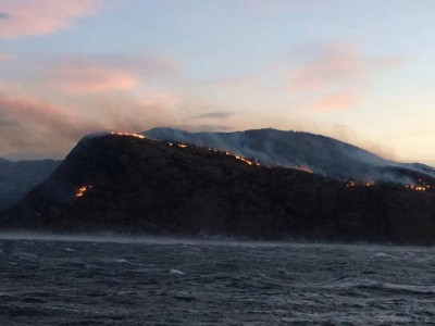 "This photo taken aboard the rescue vessel ""Harald V"" shows how the brush fire spread over hillsides on the coastal peninsula in Nord-Trøndelag, where an estimated 140 buildings were estimated to have been destroyed by midday on Tuesday. PHOTO: Redningsskøyta Harald V"