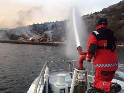 A crew member on the rescue boat RS Harald V sprays water on to the fire. While fire fighters on the ground hold containment lines and helicopters water bomb the blaze, rescue and coast guard boats are tasked with stopping the fire front jumping from the peninsula and across the bay. PHOTO: Redningsselskapet