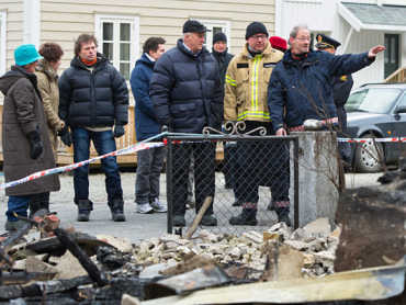 Queen Sonja (far left) and King Harald (center, in blue down jacket) visited the fire-ravaged town of Lærdalsøyri, to see the damage first-hand and lend support to residents. The king has fished for salmon in the area for years.  PHOTO: kongehuset.no/NTB Scanpix