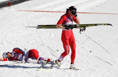 Poland's gold medal winner Justyna Kowalczyk (right) reacts after soundly beating Norway's Marit Bjørgen, who collapsed onto the snow, in the women's 10K classical-style cross-country race on Thursday at the 2014 Winter Olympics. PHOTO: AP/Matthias Schrader/NTB Scanpix