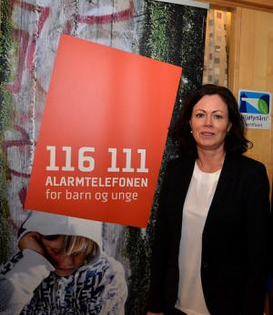 Solveig Horne, the government minister in charge of family and children's issues, with the emergency telephone number for children and youth. More measures are needed, she says, to address child abuse in Norway. PHOTO: E Johansen/BLD