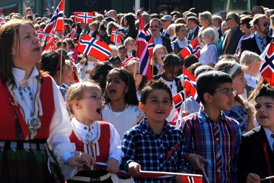 School children play an important role in 17th of May parades all over Norway, not just here in Oslo. Researchers feel the concrete roles assigned by the schools have helped fuel feelings of inclusiveness among immigrants. PHOTO: newsinenglish.no