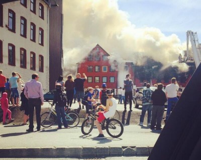 Crowds look on as fire crews battle a blaze in an old wooden warehouse by the harbour in Stavanger. The local fire department said at least two to three buildings were affected, and there was danger the blaze could spread among the close-standing buildings. PHOTO: twitter.com/OJacobsen