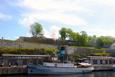 The canons at the historic Akershus Fortress and Castle were fired at precisely noon on the 17th of May, while the royals were still waving at the parade. PHOTO: newsinenglish.no
