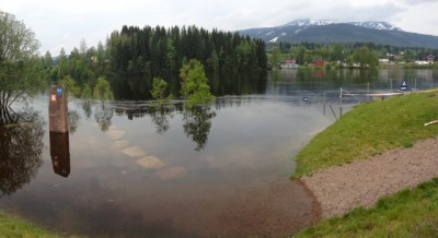 Flooding hit Trysil, a popular ski resort in the winter, over the weekend, with the flood marker at left showing rising water levels. At right, Trysil Mountain emerging from the clouds. PHOTO: Kari Hagevik Bakke / NTB Scanpix