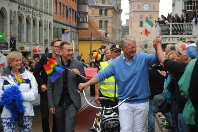 """Oslo's popular mayor (at right, in blue), Fabian Stang of the Conservative Party, clasped hands with cheering spectators along the parade route. In the background, the Oslo Cathedral, where a """"rainbow' church service was scheduled for Sunday. PHOTO: newsinenglish.no"""