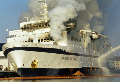 """Smoke continued to billow from the ferry """"Scandinavian Star"""" long after it was towed to a dock at Lysekil in Sweden. The tragic and unexplained fire on board the vessel after it left Oslo 24 years ago caused the heaviest loss of life in Norway since World War II. PHOTO: NTB Scanpix/Finn E Strømberg / Aftenposten"""