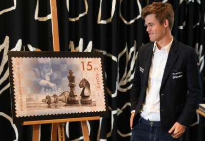 Chess star Magnus Carlsen in Tromsø on Friday, admiring the new Norwegian postage stamp that marks the national chess federation's 100th anniversary. PHOTO: Posten