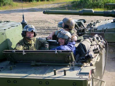Prime Minister Erna Solberg riding in a tank on a visit to military installations in northern Norway this summer. PHOTO: Forsvaret
