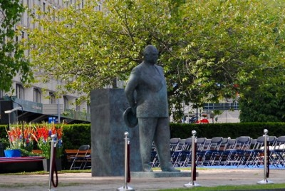 """It was easier to get a better look at the statue after the royalty and other dignitaries had left on Sunday. Sculptor Olav Orud designed a memorial that literally has King Olav stepping down from his pedestal, wearing a suit instead of a gala uniform and holding his hat in his hand. The idea is to portray Olav as a """"down to earth"""" monarch who was """"the people's king."""" Adorning the pedestal are images of Olav arriving as a three-year-old in Norway in 1905 and returning after the war in 1945, while the other two sides show him skiing and sailing, he favourite pursuits. PHOTO: newsinenglish.no"""