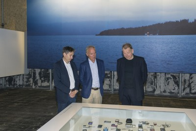 Government minister Jan Tore Sanner (center) reviewing a display of the mobile phones found scattered around the island of Utøya after their young owners were killed. Many of them contained desperate calls for help and text messages to loved ones. In the background, a photo of the island where 69 people were killed and scores more wounded in the lone gunman's massacre. PHOTO: KMD/Ann Kristin Lindaas