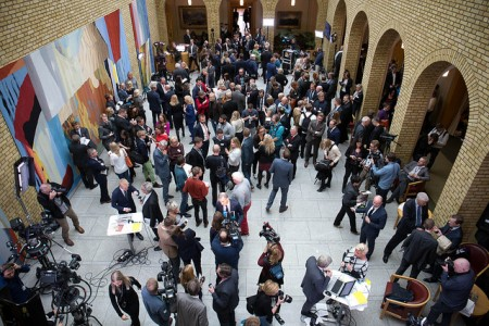 """This is the hall inside Norway's Parliament known as """"Vandrehallen,"""" where politicians and lobbyists gather to meet reporters and debate issues. This was the scene after Wednesday's release of the state budget, when many involved were keen to comment, praise it or pick it apart. Finance Minister Siv Jensen can be seen in the lower right-hand corner, defending what she'd just presented. PHOTO: Arbeiderpartiet"""