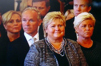 Prime Minister Erna Solberg smiled while King Harald was reading aloud her government's proclamation at the opening of Parliament. Finance Minister Siv Jensen (right) looked far more glum, perhaps worrying about the state budget she'll need to present next week. PHOTO: NRK screen grab/newsinenglish.no