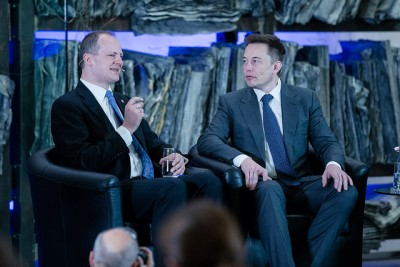 Tesla founder Elon Musk in conversation with Norwegian Transport Minister Ketil Solvik-Olsen in Oslo on Thursday. Musk thanked Norwegian officials for providing the incentives that have made electric cars so popular and prevalent in Norway. They've also made him even wealthier in the process. PHOTO: Samferdselsdepartementet
