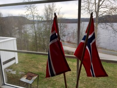 Flags were already set up before breakfast in the window of a guest house near Norway's border to Russia, which can be seen in the distance across the lake. PHOTO: newsinenglish.no