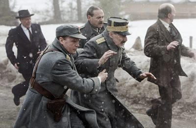 """King Haakon VII (played by Danish actor Jesper Christensen) flees a German bombing raid with his son Crown Prince Olav (Anders Baasmo Christiansen) after delivering his historic """"no"""" to any form of royal cooperation with Nazi German invaders during World War II. PHOTO: Filmweb/Agnete Brun"""