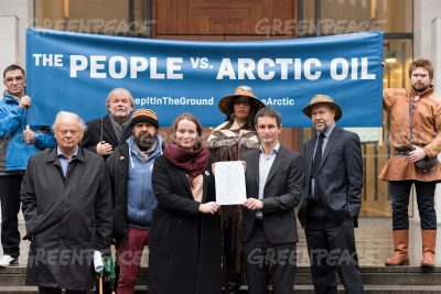 Ingrid Skjoldvær, head of Nature and Youth, and Truls Gulowsen, head of Greenpeace Norway, hold their legal claim against the Norwegian government while posing with supporters including author Jostein Gaarder (back row, at left). PHOTO: Greenpeace/Christian Åslund