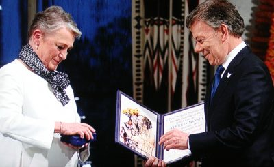 Berit Reiss-Andersen of the Norwegian Nobel Committee opens the box containing the gold medal to this year's prizewinner, Colombian President Juan Manuel Santos. The artwork on this year's diploma is meant to represent forgiveness. PHOTO: NRK screen grab
