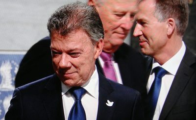 """This year's Nobel Peace Prize winner noted during his stay in Osllo that """"sometimes you have to make war in order to make peace."""" Kissinger would likely agree and Santos greeted his new fellow Nobel Laureate during the weekend. In the background, Norway's King Harald (center) and Olav Njølstad, the director of the Nobel Institute who has been criticized for inviting Kissinger to speak at the University of Oslo n Sunday. PHOTO: NRK screen grab"""