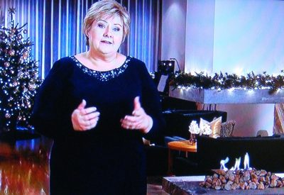 Prime Minister Erna Solberg spoke while standing in the living room of her official residence, with a Christmas tree lit in the background and a fire in the fireplace to add to the ambiance. PHOTO: NRK screen grab